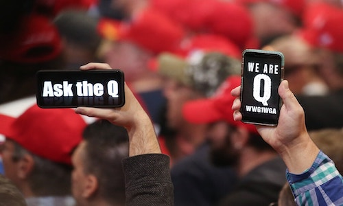 Hands holding up cellphones showing Q on the screens (for QAnon).